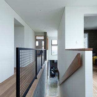 Exemple d'un escalier droit moderne avec des marches en bois, des contremarches en béton, un garde-corps en métal et un mur en parement de brique.