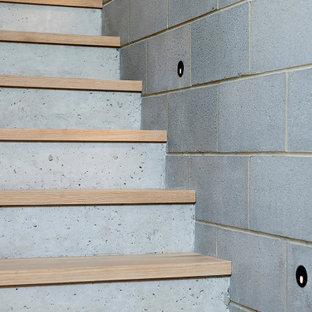 Imagen de escalera recta y ladrillo, minimalista, con escalones de madera, contrahuellas de hormigón, barandilla de metal y ladrillo