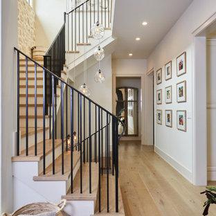 Foto på en mellanstor funkis l-trappa i trä, med sättsteg i målat trä och räcke i metall