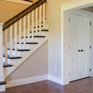 Diseño de escalera en L, de estilo americano, con escalones de madera, contrahuellas de madera pintada y barandilla de madera