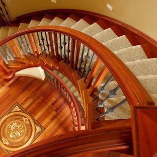 Ejemplo de escalera en U, clásica, grande, con escalones enmoquetados, contrahuellas de madera y barandilla de varios materiales