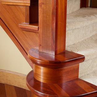 エドモントンの大きいカーペット敷きのトラディショナルスタイルのおしゃれな折り返し階段 (木の蹴込み板、混合材の手すり) の写真
