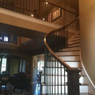 Idée de décoration pour un grand escalier courbe design avec des marches en bois, des contremarches en bois peint et un garde-corps en métal.