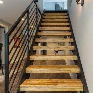 Bild på en stor funkis rak trappa i trä, med öppna sättsteg och räcke i metall
