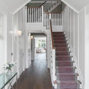 ダブリンの小さい木のトランジショナルスタイルのおしゃれなかね折れ階段 (木の蹴込み板、木材の手すり) の写真