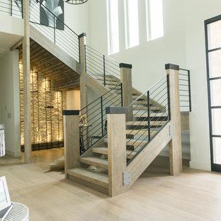 """Esempio di una grande scala a """"U"""" design con pedata in legno, nessuna alzata e parapetto in metallo"""