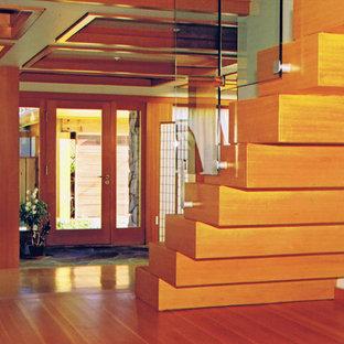 Immagine di una scala sospesa minimal di medie dimensioni con pedata in legno, alzata in legno e parapetto in vetro