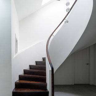 Photo of a transitional wood curved staircase in Sydney.