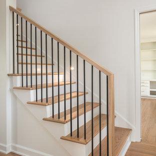 Immagine di una scala a rampa dritta minimal di medie dimensioni con pedata in legno, alzata in legno verniciato e parapetto in metallo