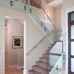 バンクーバーのカーペット敷きのコンテンポラリースタイルのおしゃれな折り返し階段 (カーペット張りの蹴込み板、ガラスの手すり) の写真