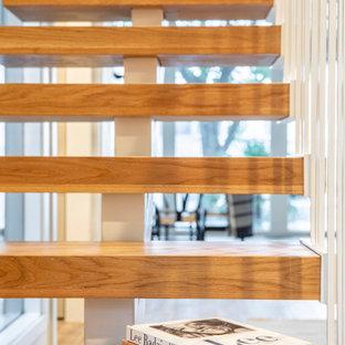 Esempio di una scala sospesa moderna di medie dimensioni con pedata in legno, alzata in metallo e parapetto in metallo