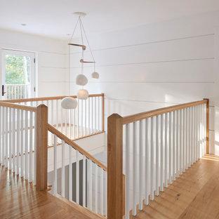 """Esempio di una scala a """"L"""" stile marinaro di medie dimensioni con pedata in legno, alzata in legno e parapetto in legno"""