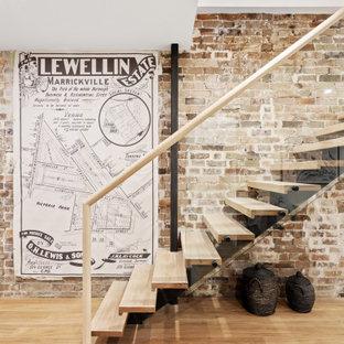 Moderne Holztreppe mit offenen Setzstufen, Glasgeländer und Ziegelwänden in Sydney