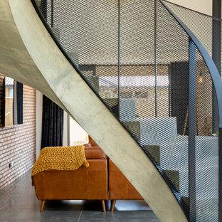 Immagine di una grande scala a chiocciola moderna con pedata in cemento, alzata in cemento e parapetto in metallo