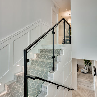 Large coastal carpeted u-shaped glass railing staircase in Miami with carpeted risers.