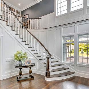Imagen de escalera curva y panelado, tradicional renovada, grande, con escalones de madera, contrahuellas de madera pintada, barandilla de madera y panelado