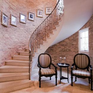 На фото: большая изогнутая лестница в стиле фьюжн с ступенями из известняка, подступенками из известняка и металлическими перилами с