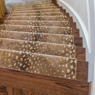Ispirazione per una scala curva eclettica di medie dimensioni con pedata in legno, alzata in legno e parapetto in legno
