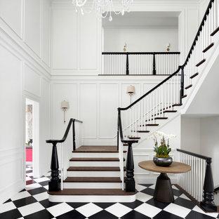 Imagen de escalera en U y panelado, clásica renovada, con escalones de madera, contrahuellas de madera pintada y panelado