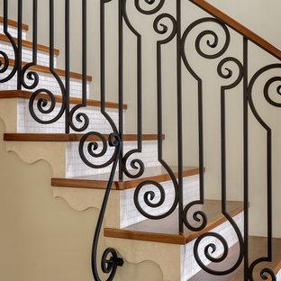 На фото: прямая лестница среднего размера в средиземноморском стиле с деревянными ступенями и подступенками из плитки с