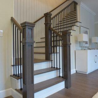 Ejemplo de escalera en L y machihembrado, de estilo americano, de tamaño medio, con escalones de madera pintada, contrahuellas de madera, barandilla de madera y machihembrado