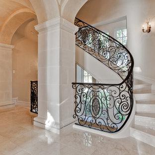 Diseño de escalera curva, mediterránea, grande, con escalones de mármol, contrahuellas de mármol y barandilla de metal