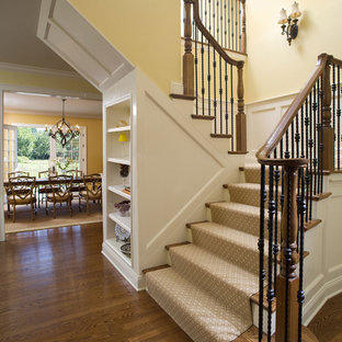 Elegant wooden u-shaped mixed material railing staircase photo in New York with carpeted risers