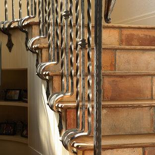 Пример оригинального дизайна: лестница в классическом стиле с подступенками из терракотовой плитки, металлическими перилами и деревянными ступенями