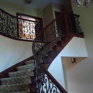 Imagen de escalera curva, clásica, de tamaño medio, con escalones enmoquetados, contrahuellas enmoquetadas y barandilla de madera