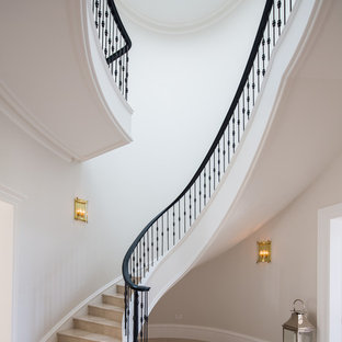Example of a huge classic marble curved metal railing staircase design in London with marble risers
