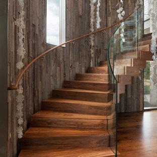 Modelo de escalera curva, rústica, con escalones de madera, contrahuellas de madera y barandilla de vidrio