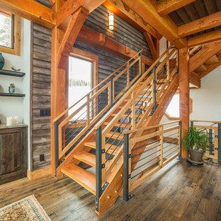 "Foto di una scala a ""L"" rustica di medie dimensioni con pedata in legno, nessuna alzata e parapetto in cavi"