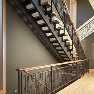 Foto di una scala a rampa dritta moderna di medie dimensioni con pedata in legno e nessuna alzata