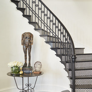 Example of a classic wooden curved wood railing staircase design in Seattle with wooden risers