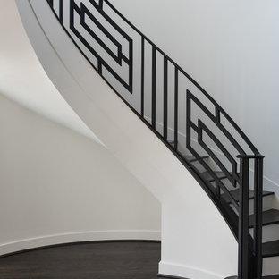 Diseño de escalera curva, actual, con escalones de madera y contrahuellas de madera pintada