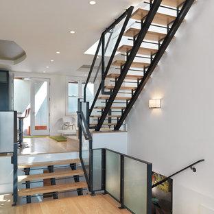 Inspiration pour un escalier sans contremarche nordique avec des marches en bois et un garde-corps en verre.