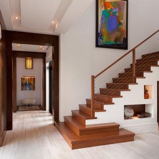 Foto de escalera en L, contemporánea, de tamaño medio, con escalones de madera, contrahuellas de madera y barandilla de cable