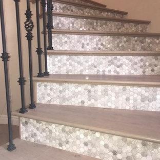 Modelo de escalera curva, actual, grande, con escalones de madera, contrahuellas con baldosas y/o azulejos y barandilla de varios materiales