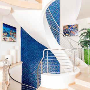 Ejemplo de escalera de caracol, actual, grande, con barandilla de metal, escalones con baldosas y contrahuellas con baldosas y/o azulejos