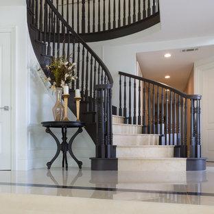 Inspiration för stora klassiska svängda trappor i travertin, med sättsteg i travertin och räcke i trä