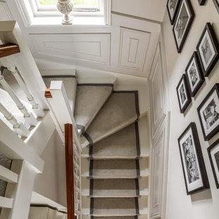 Ejemplo de escalera en U y panelado, tradicional renovada, grande, con escalones de madera pintada, contrahuellas de madera pintada, barandilla de madera y panelado