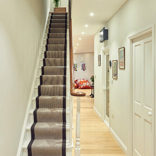 Photo of a small classic painted wood straight staircase in London with painted wood risers.