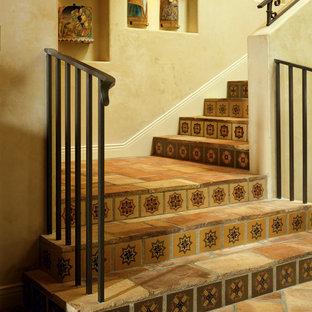 Foto de escalera mediterránea con escalones de terracota, contrahuellas con baldosas y/o azulejos y barandilla de metal