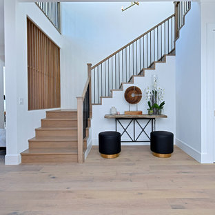 Example of a transitional wooden u-shaped mixed material railing staircase design in Los Angeles with wooden risers