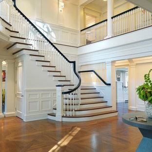Foto de escalera curva, clásica, grande, con escalones de madera, contrahuellas de madera pintada y barandilla de madera