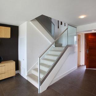 オレンジカウンティの小さいカーペット敷きのモダンスタイルのおしゃれな折り返し階段 (カーペット張りの蹴込み板、ガラスの手すり) の写真