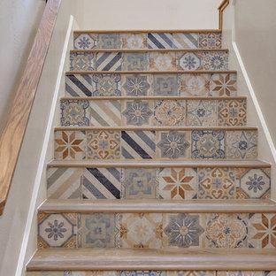 """Idee per una grande scala a """"L"""" mediterranea con pedata in legno, alzata piastrellata e parapetto in legno"""