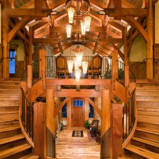 Immagine di un'ampia scala curva stile rurale con pedata in legno e alzata in legno