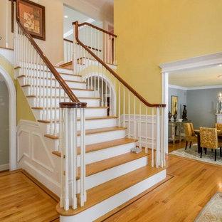 Diseño de escalera recta, clásica, grande, con escalones de madera, contrahuellas de madera pintada y barandilla de madera