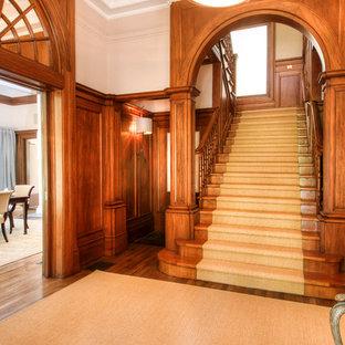 サンフランシスコの広い木のトラディショナルスタイルのおしゃれな折り返し階段 (木の蹴込み板) の写真